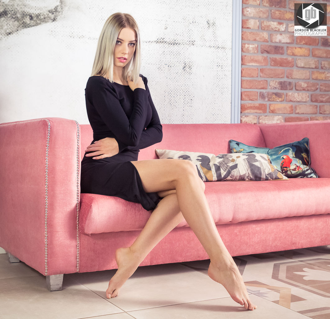 beautiful blonde woman in a short black dress sits on pink sofa