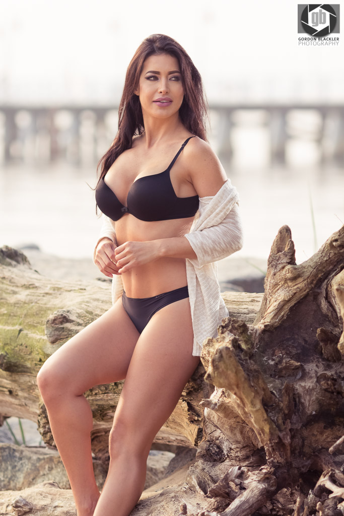 beautiful brunette leans against a tree at the beach in sopot, poland