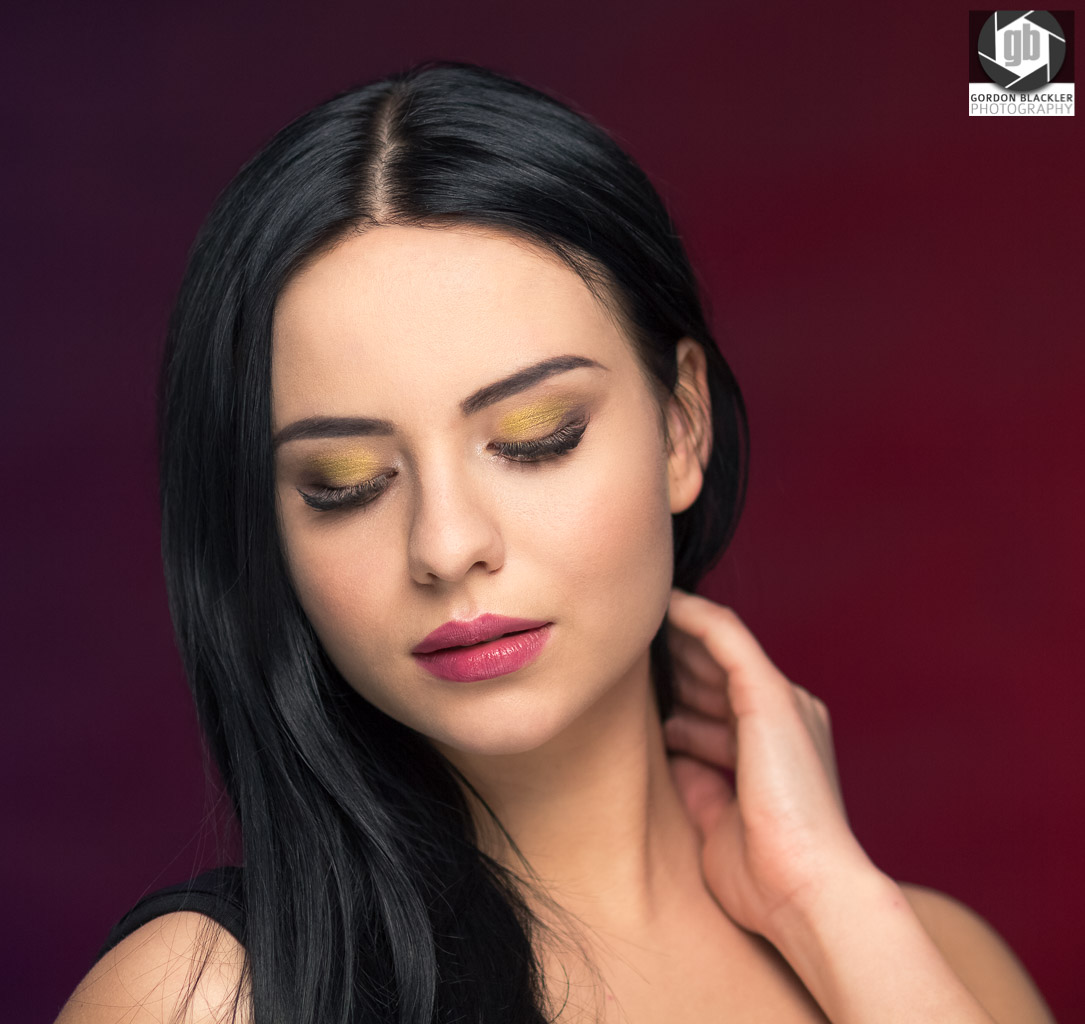 studio portrait of beautiful brunette who looks down holds her neck