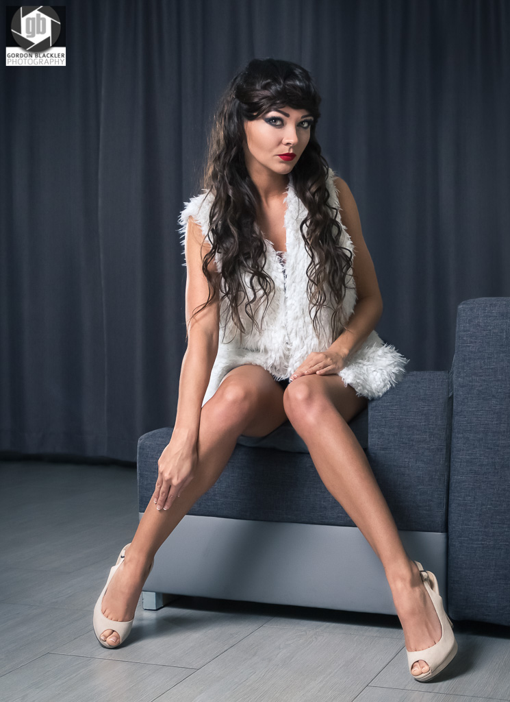 fashion portrait of brunette in white fur waistcoat sitting on sofa
