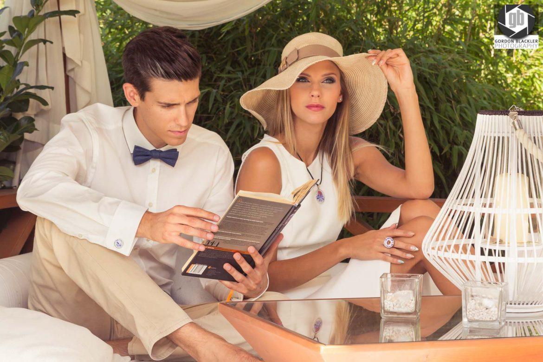 lifestyle fashion portrait of stylish couple sitting under gazebo