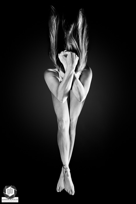 fine art implied nude, black and white, low key, woman with arms and legs crossed
