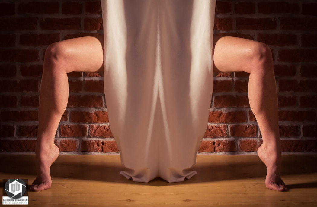 conceptual photo of legs on tiptoe hiding behind curtain
